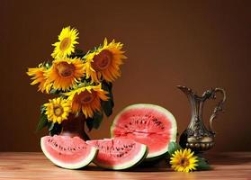 Sunflowers in a vase and fresh watermelon photo