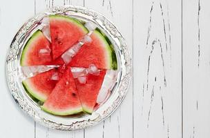 Slices of ripe organic watermelon, served on vintage silver tray