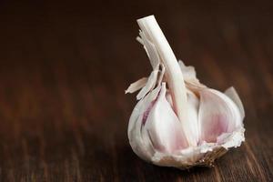 Garlic bulb resting on wood chopping board