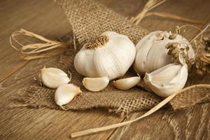 Organic garlic whole and cloves on the wooden background photo