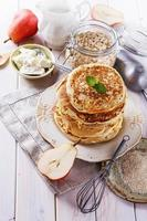 Healthy oat pancakes over white wooden background