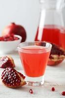 Pomegranate juice in glass and pitcher