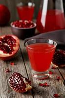 Pomegranate juice in glass on grey wooden background