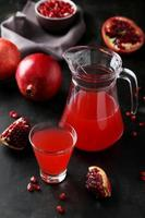 Pomegranate juice in glass and pitcher on grey wooden background