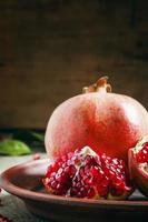 Juicy red cleared pomegranate on a clay plate photo