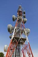 Telecommunications tower against blue sky photo