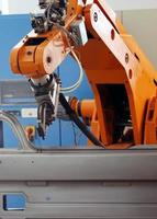 An orange electronic robot arm on an assembly line photo