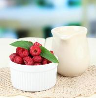 Fresh raspberry  and cream in jug on bright background