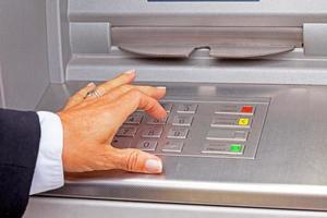 Entering pin code in the cash machine photo