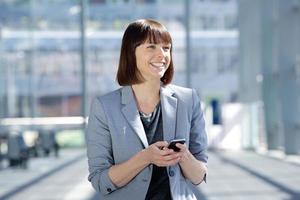 sonriente mujer de negocios caminando con teléfono celular foto