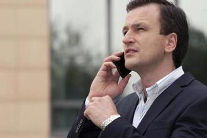 Retrato de hombre de negocios mediante teléfono celular foto