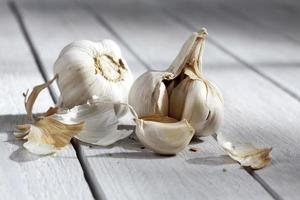Garlic bulb and cloves on gray wooden background photo