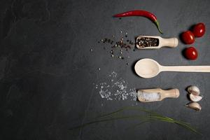 Wooden spoon and spices on stone background