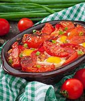 Baked tomatoes with garlic and eggs