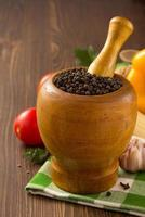 mortar with pestle and spices on wood photo