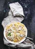 Pasta spaghetti with creamy mushroom sauce and basil in white photo