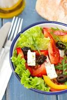 salad in bowl with bread and oil on blue background photo