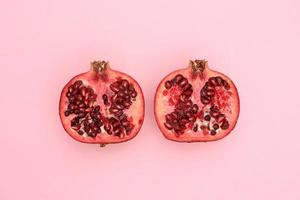 Fresh pomegranate cut in half on pink background photo