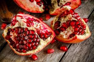 Ruby pomegranate open with seeds closeup on wooden table