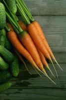 cosecha fresca de zanahorias y pepinos foto