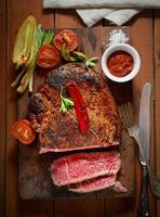 steak on the wooden background with roasted vegetables photo