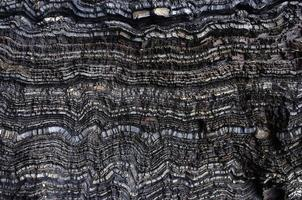 Black wavy layers of rock