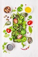 Ensalada con tomates, aceitunas, aceite y vinagre en madera blanca