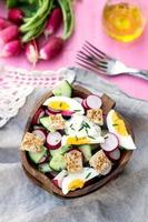 Salad with radish, cucumber, eggs and bread croutons photo