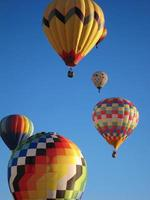 Hot air balloons float in blue cloudless sky photo