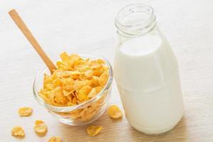 Bowl of cornflake and milk bottle