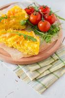 Polenta - traditional corn dish with cherry tomatoes and ruccola photo