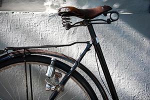 Detalle de un asiento de bicicleta vintage, rueda, dinamo y cerradura