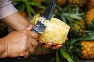 Peeling a pineapple photo
