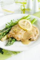 Grilled veal chop with lemony sauce and asparagus photo