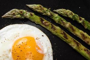 huevo frito y espárragos asados en placa negra