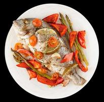 Roasted gilt-head bream with vegetables isolated on black photo