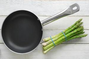 Bunch of fresh asparagus next to a frying pan