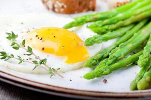 Green asparagus,fried egg and bread with butter.