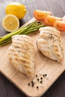 Marinated grilled chicken breasts on the wooden table