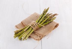 Bunch of asparagus on a white wooden background photo