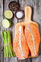 fresh raw salmon fillet on cutting board with asparagus
