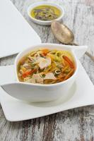 rustic chicken soup with noodles and over wooden background photo