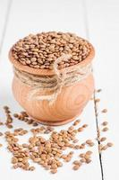 Dry Organic Brown Lentils against a wooden background photo