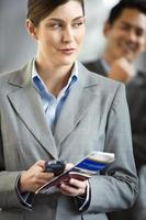 Businesswoman in airport terminal, holding phone and ticket photo