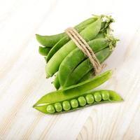 Gousse de pois verts sur une table en bois blanche