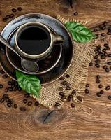 black coffee with beans and green leaves on wooden background