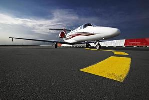 A small business jet on a runway from a ground view photo