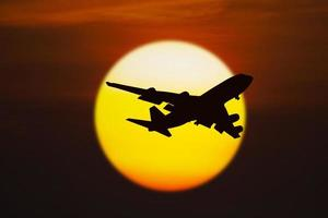 Silhouette of airplane on sunset photo