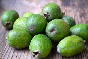 Green feijoa fruit on wooden table photo