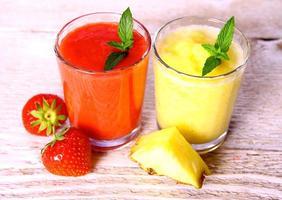 fresa, licuado de piña en vaso, menta, rodaja de piña foto